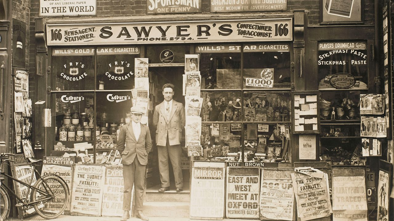 A photograph of two newsagents outside their shop front soon after World War One