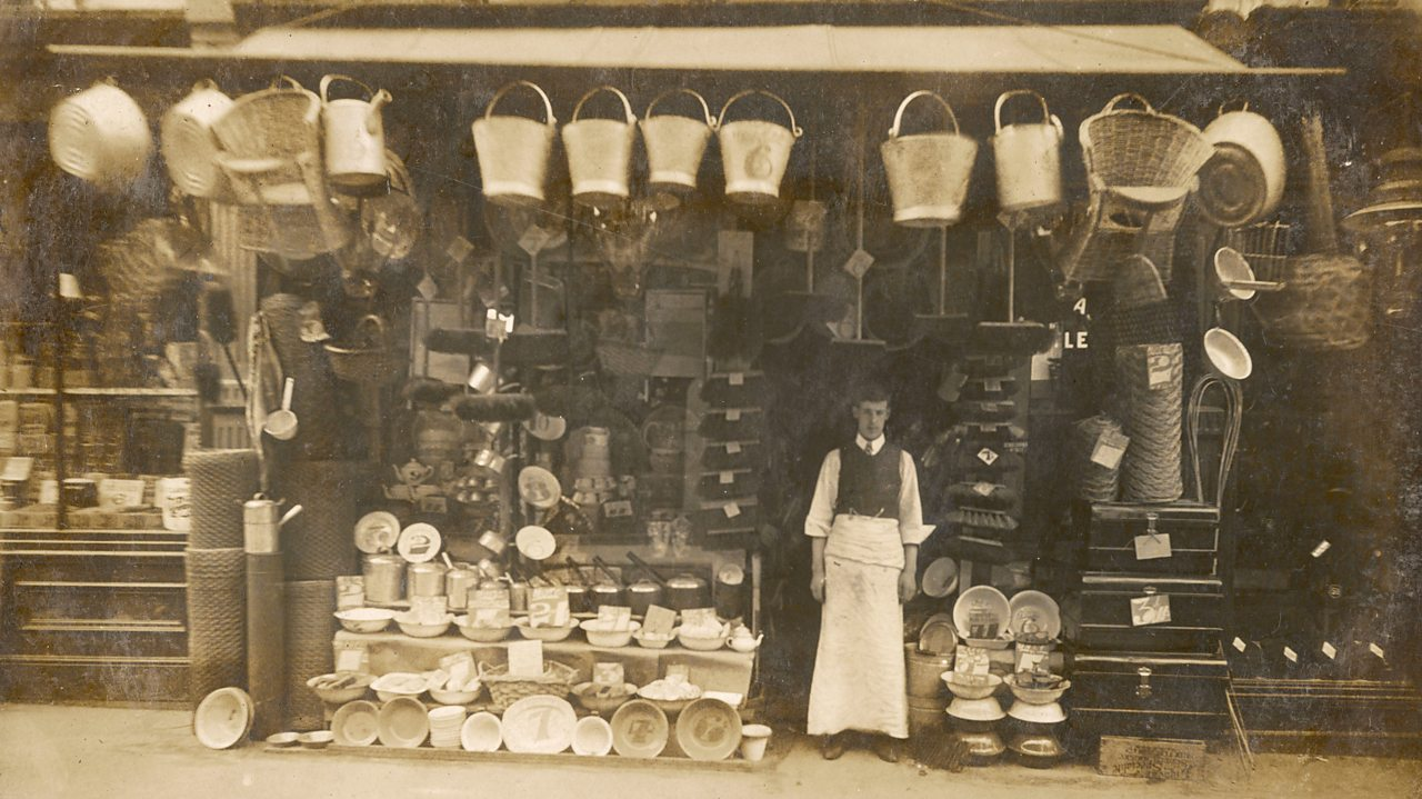 A photograph of an ironmonger outside his shop front in World War One