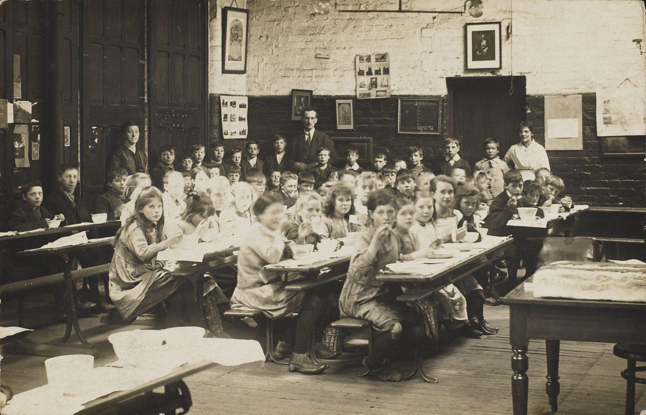 Children eating school dinner in a classroom during World War One