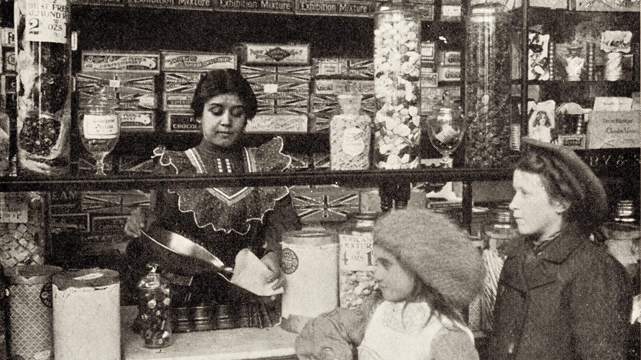A shopkeeper serving sweets to two children in the early 1900s