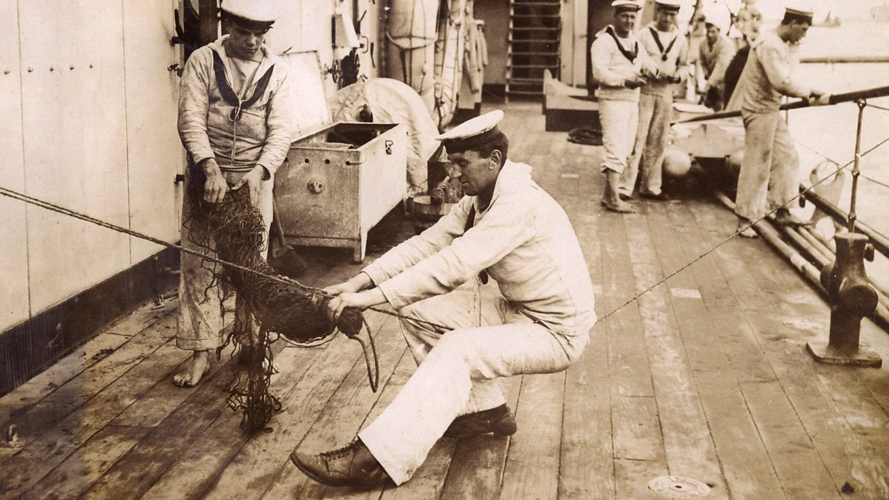 Two sailors working on a net while others watch on a ship in World War One