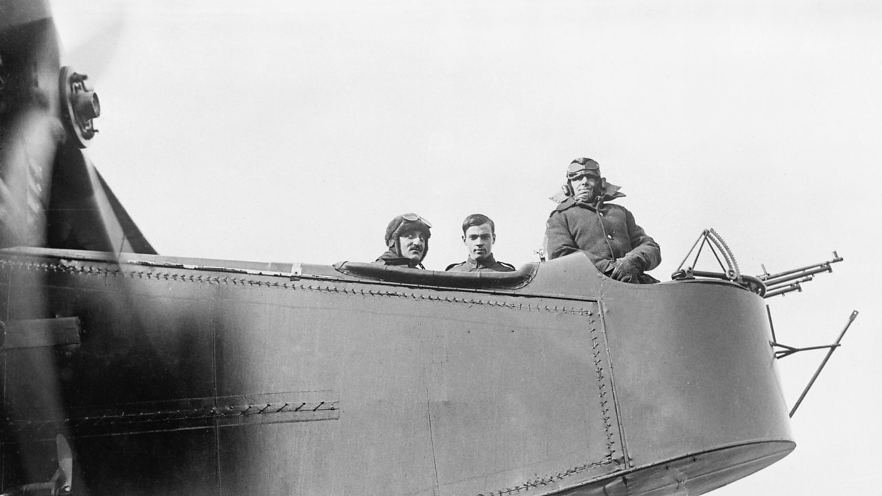 Three airforce men looking out from a plane in World War One