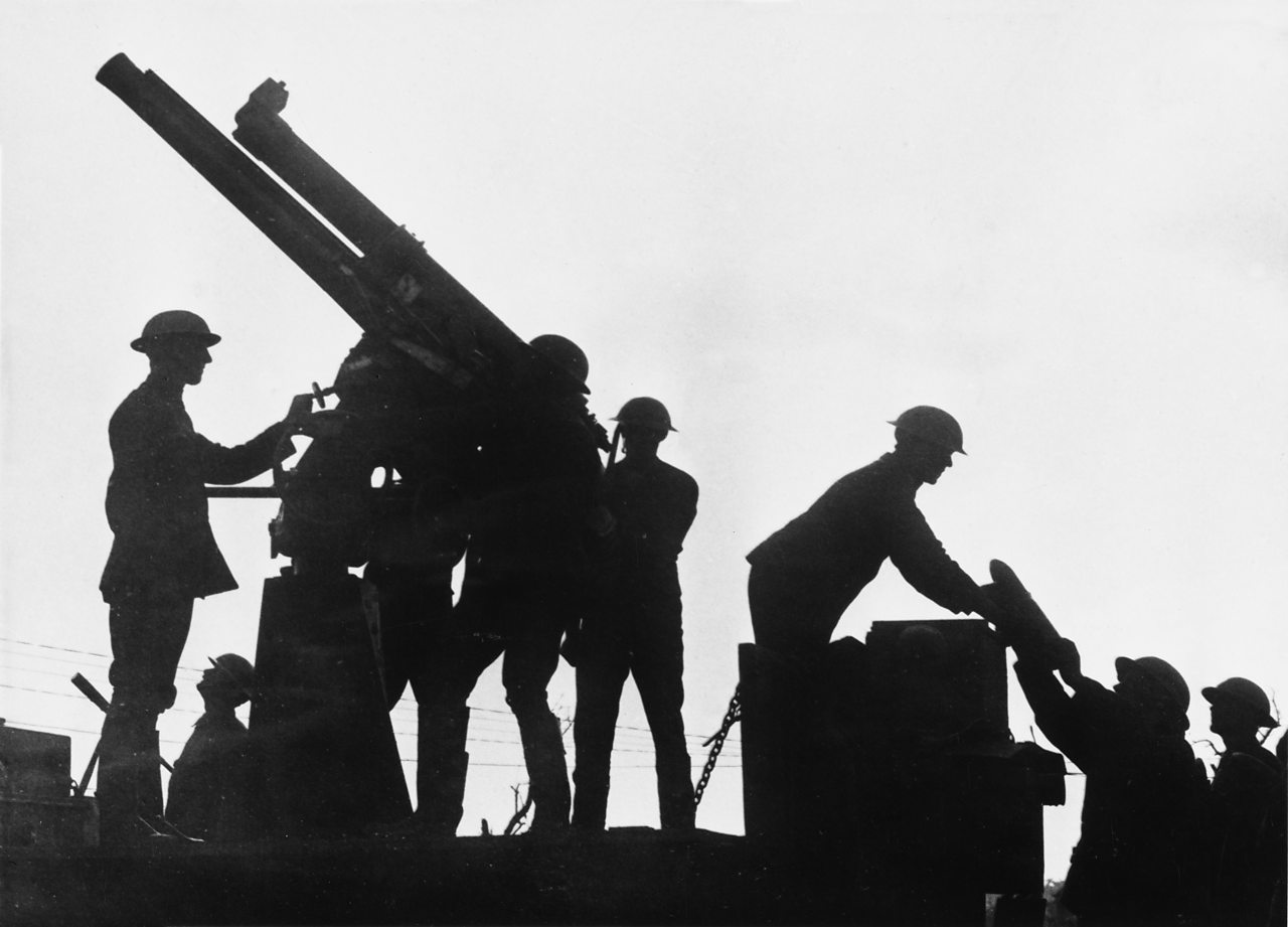 World War One soldiers in silhouette loading a weapon