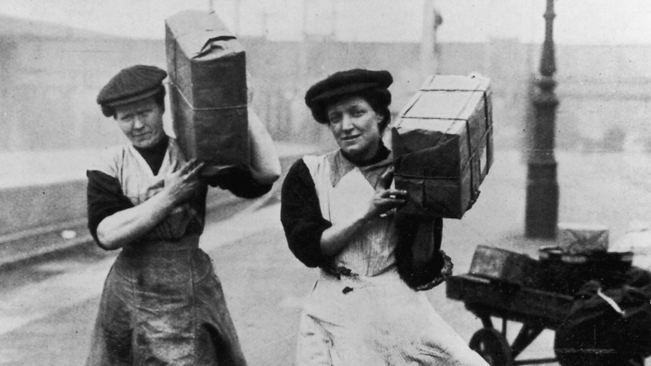 Two British women carry packages while they work as porters in London in 1915