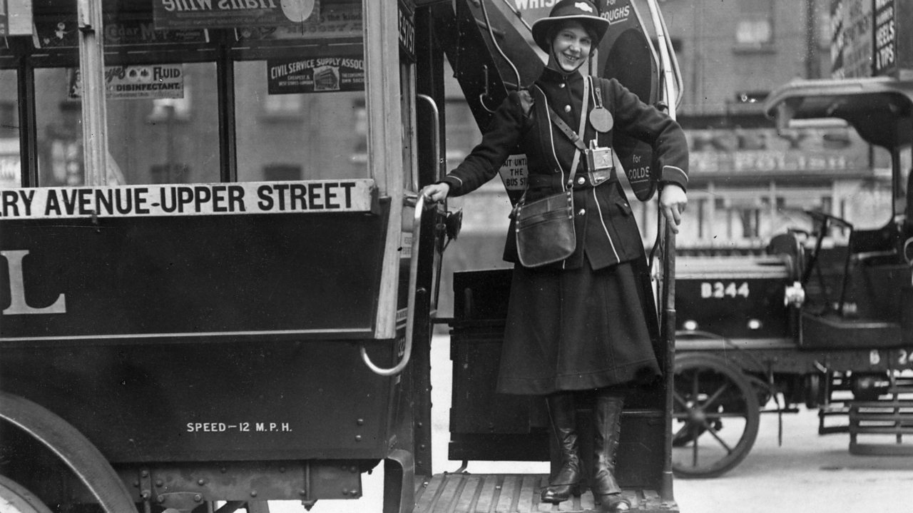 A bus conductor greeting her passengers during World War One