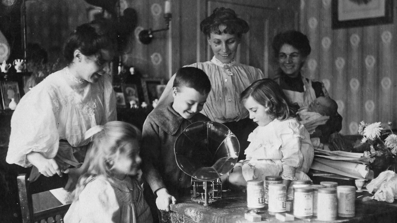 A housewife and servants watch children gather around a gramophone in the early 1900s