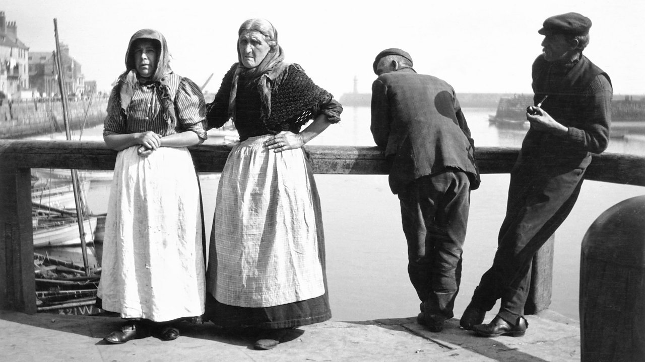 Two fishwives standing with two men on a pier cart in the early 1900s