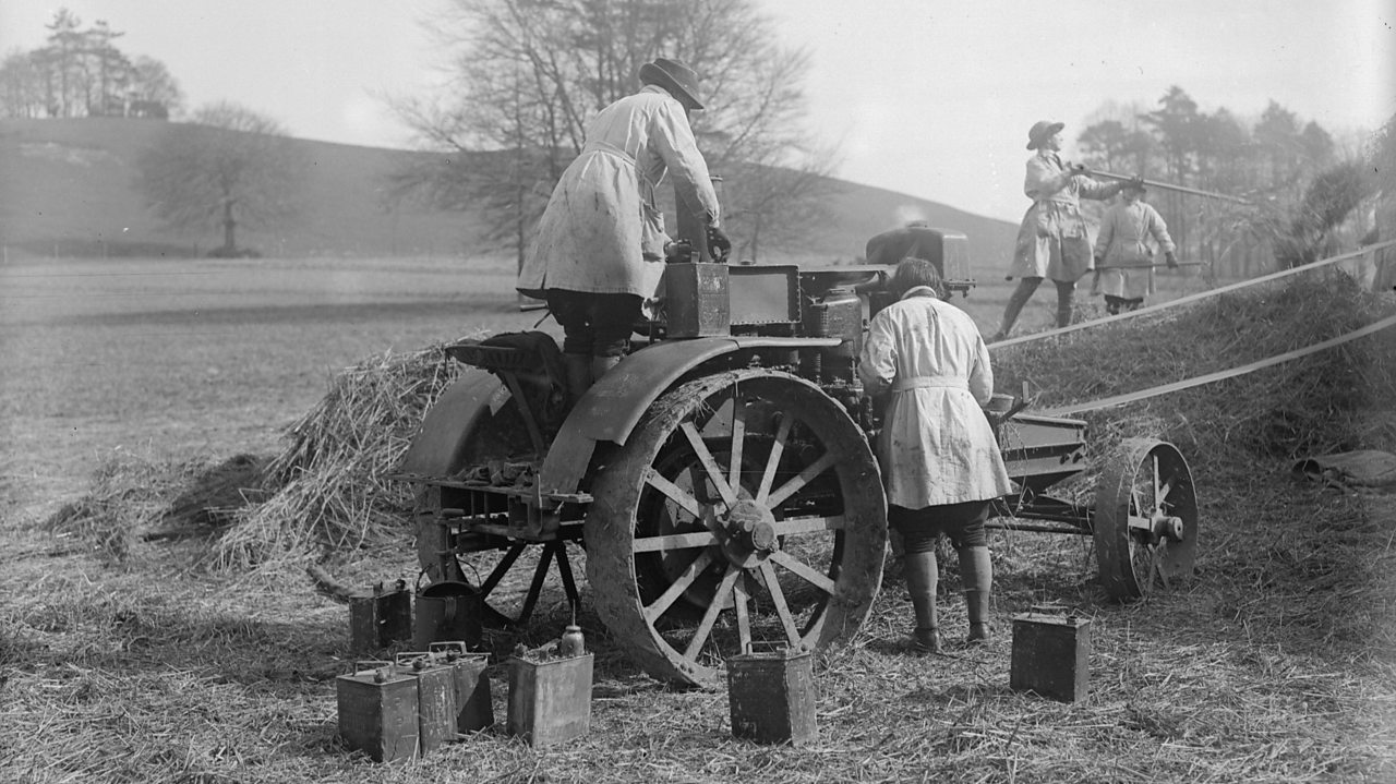 Women working on agricultural machinery in March 1918 as part of their training to be Land Girls