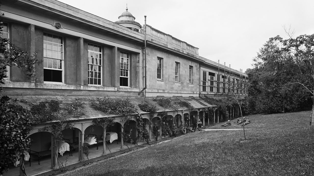 The outside of the military hospital at Woburn Abbey showing beds on a veranda and wounded soldiers relaxing in World War One