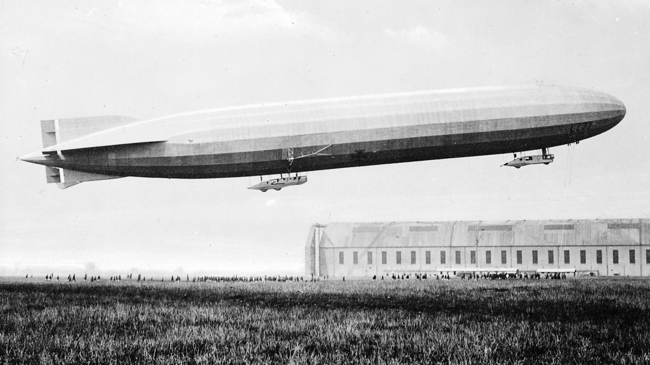 A German Zeppelin airship in flight above an air field