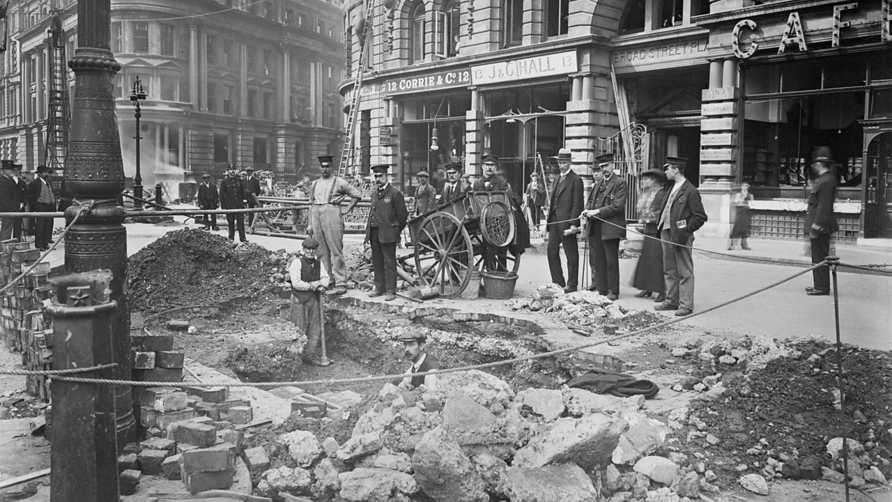 A group of men stand around a bomb damaged street the day after an air raid during World War One