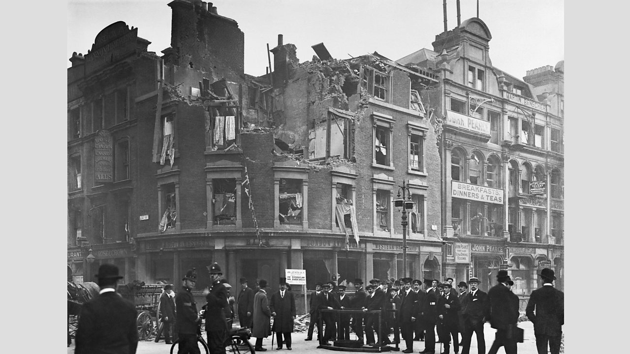 Police and a group of men stand beside a badly damaged building in Aldgate, London in World War One