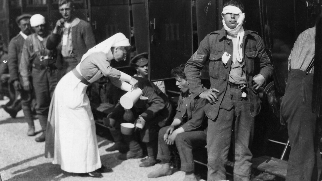 A World War One nurse serving tea to wounded British soldiers beside a railway carriage