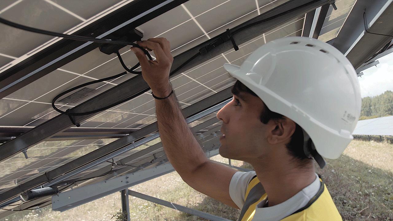 A young man checks cables at a solar power farm
