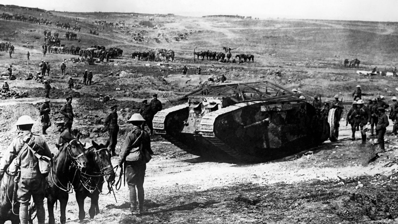 A tank on a barren battlefield with soldiers in World War One