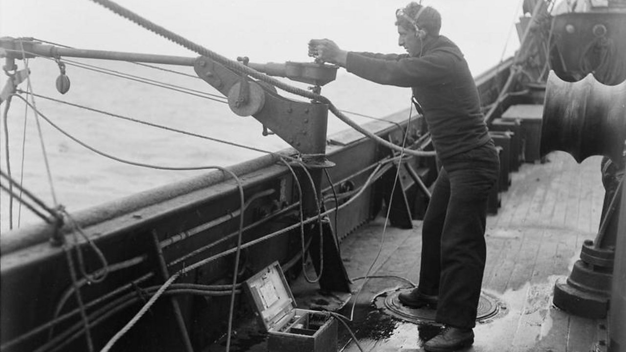 An operative uses a hydrophone on a boat in World War One