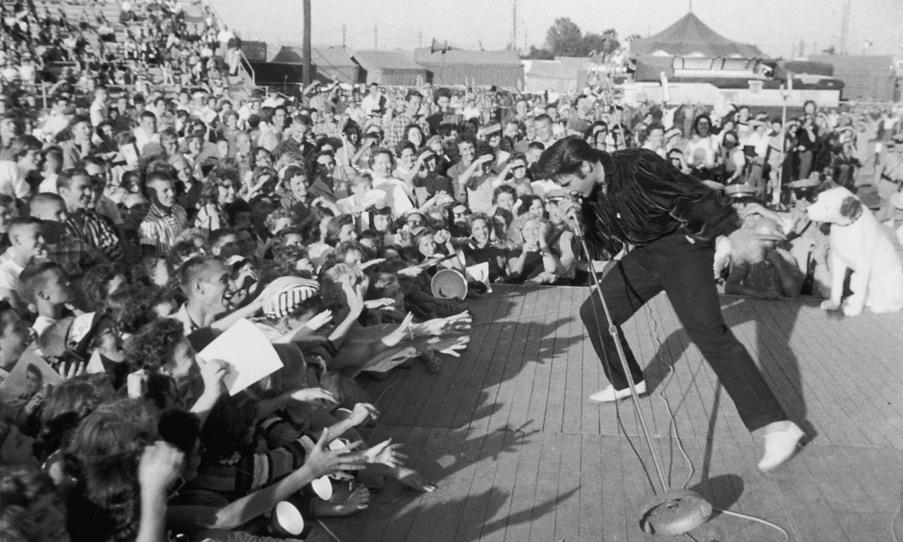Elvis Presley performs to adoring fans in his hometown of Tupelo, Mississippi, 1957.