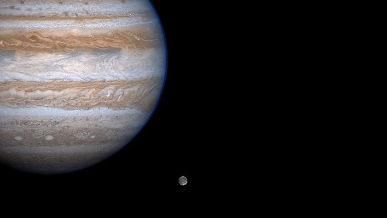 A photo of Jupiter and its largest moon Ganymede, taken from the Cassini spacecraft