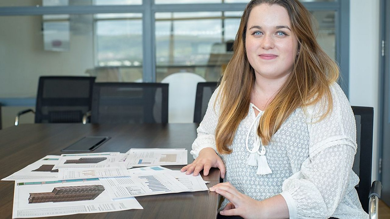 a young woman sits at a desk in an office with papers in front of her