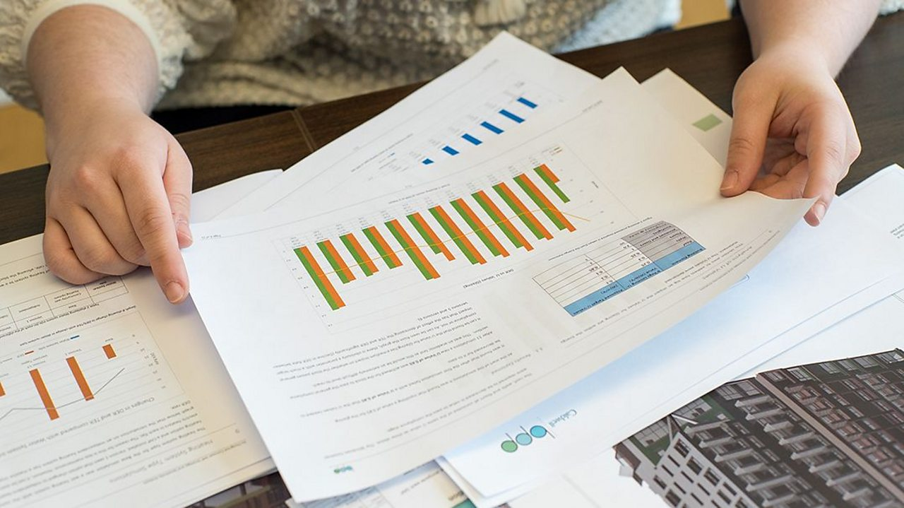 Papers on a desk display graphs