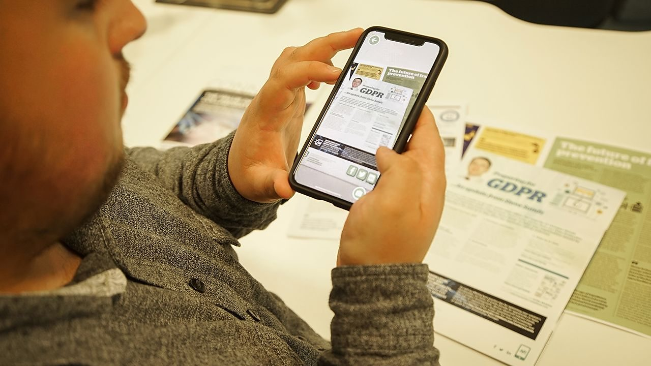 A man takes a photograph of some documents on his phone screen, testing an app