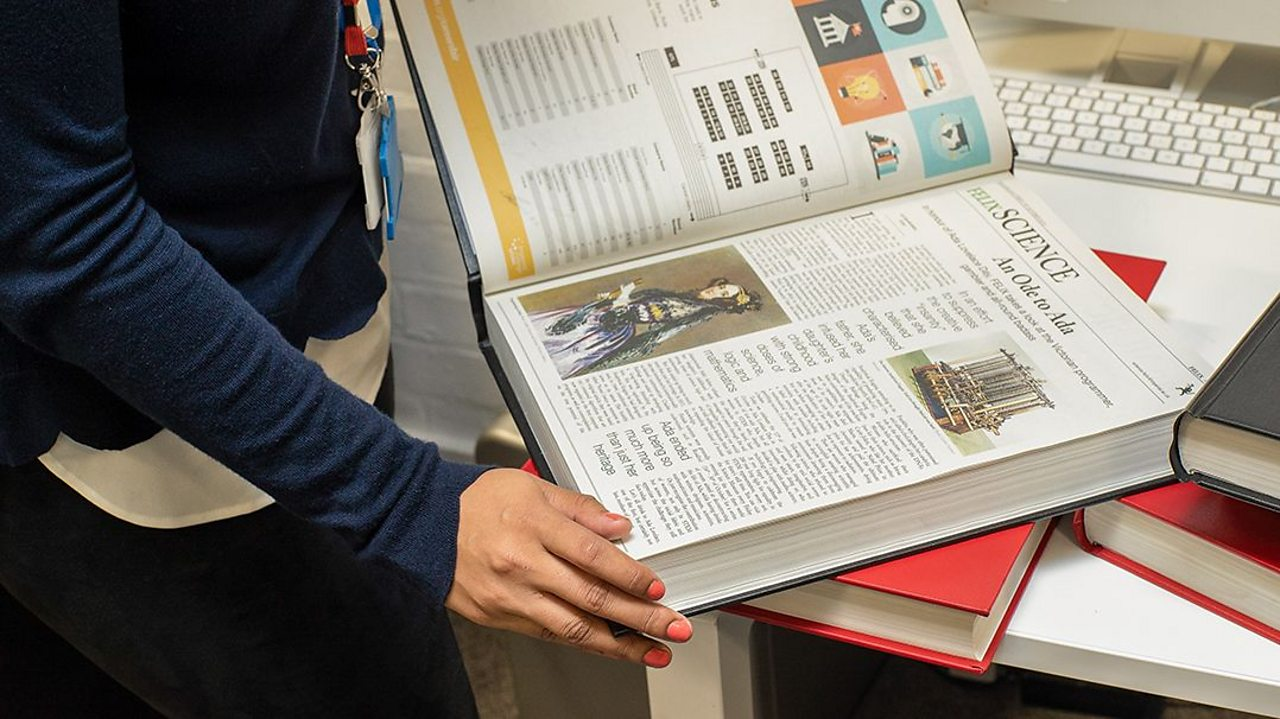 A science journal is held open, displaying articles on a table