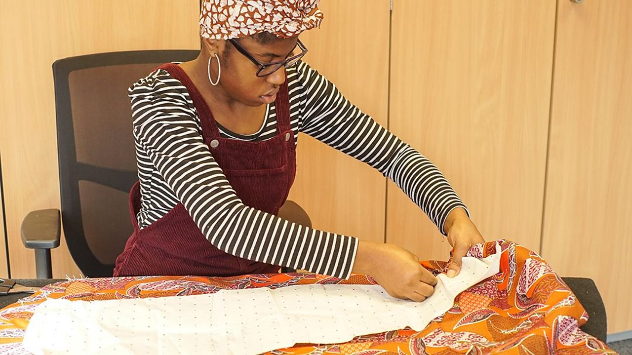 a young woman pins a sewing pattern to a piece of bright coloured fabric