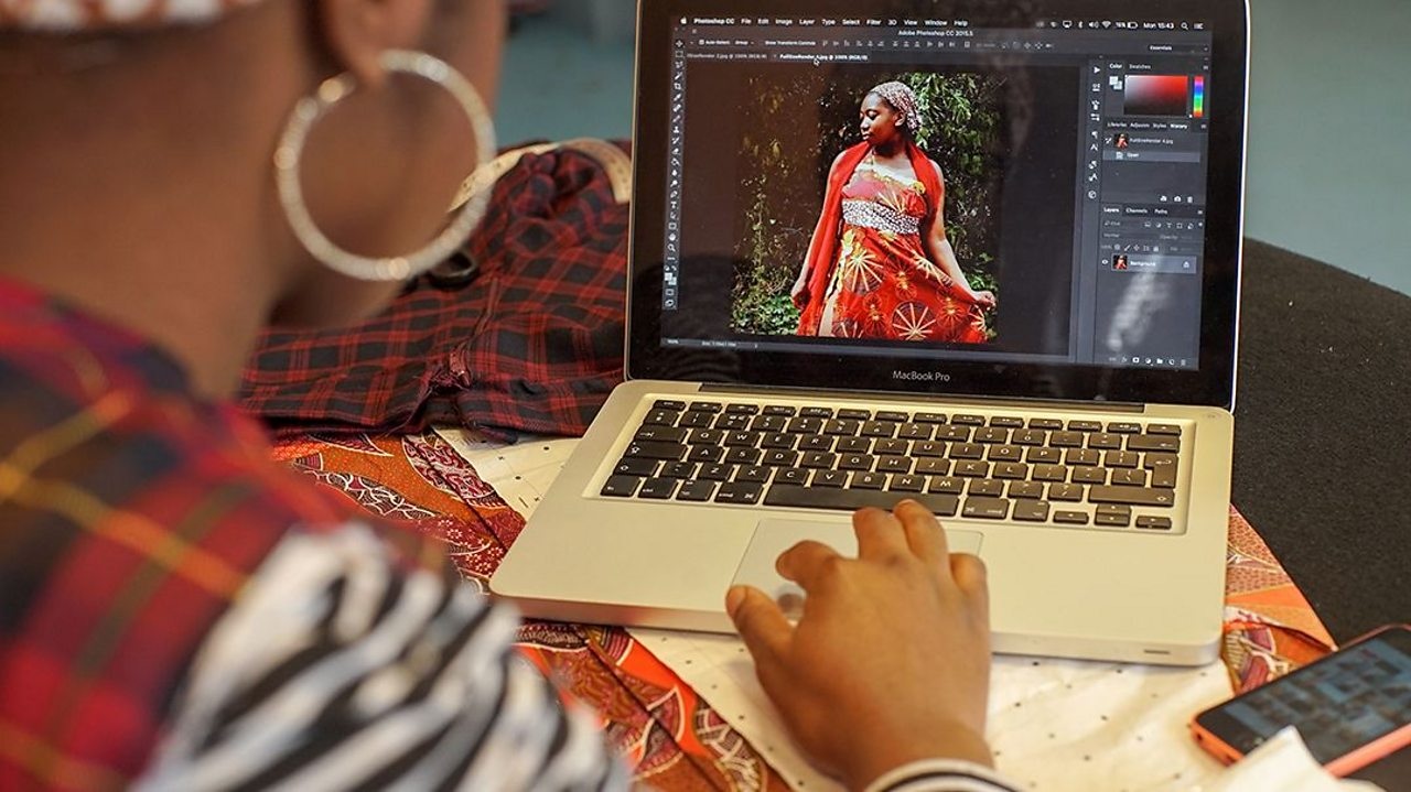 a young woman views photos of a fashion model, wearing the clothes she has designed on a laptop