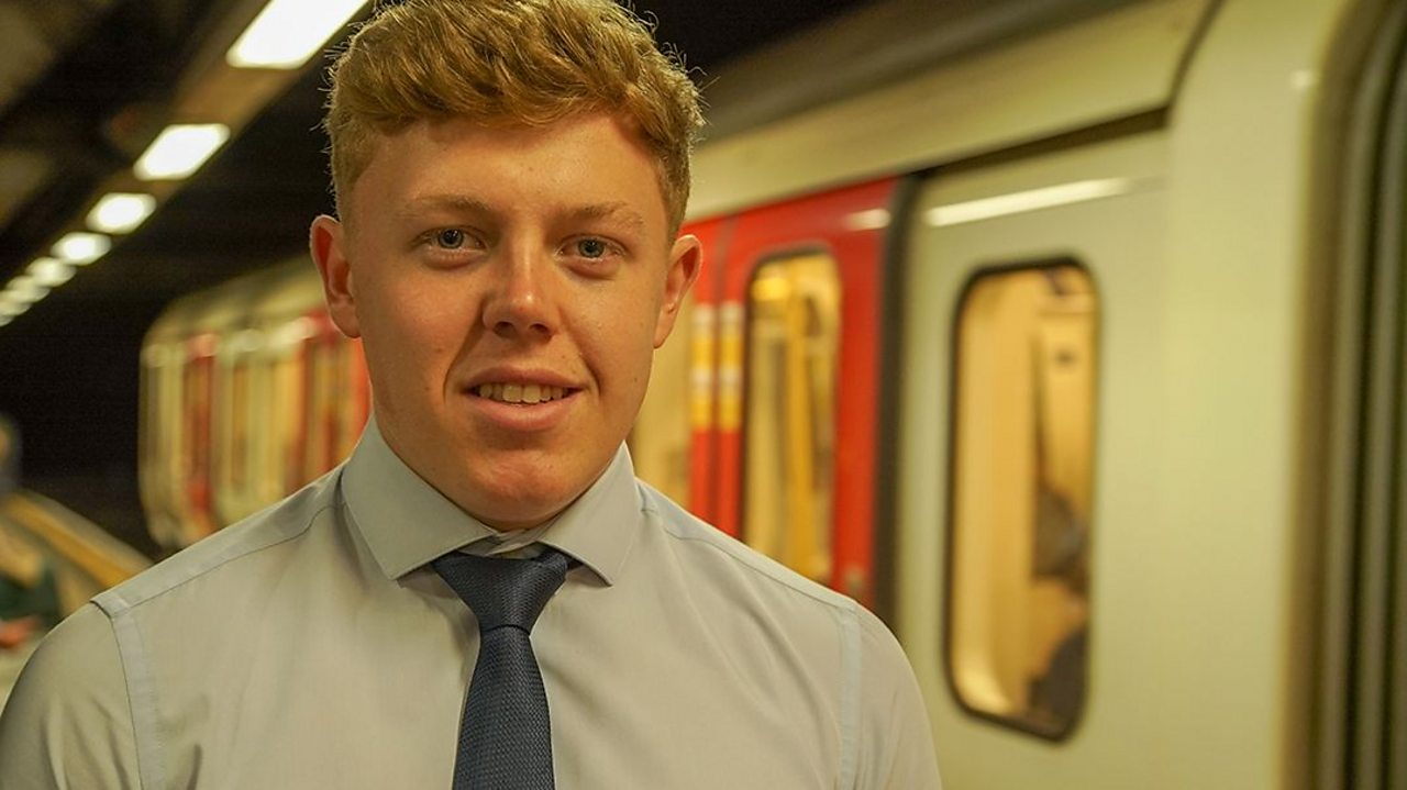 a young man stands on the platform next to a tube train in a London station