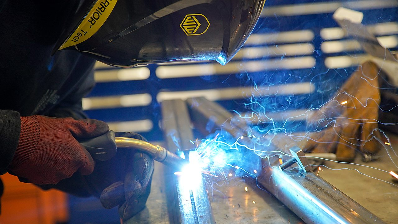 A young man, Billy, is shown welding