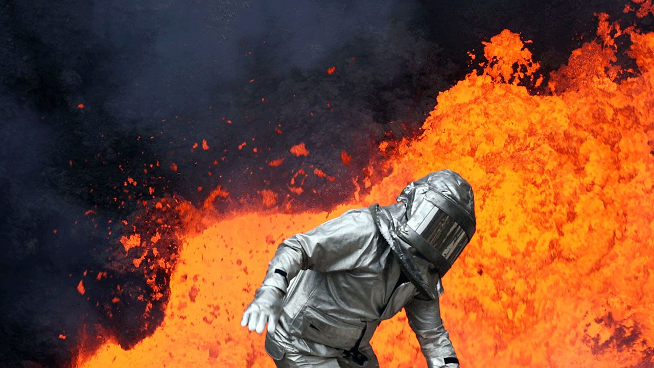 A figure in a safety suit in front of molten lava.