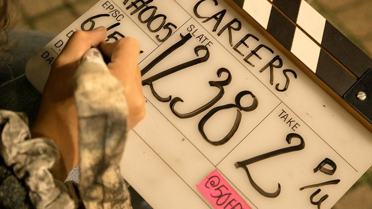 Tamsin writes a scene description on a clapper board that reads 'Careers'