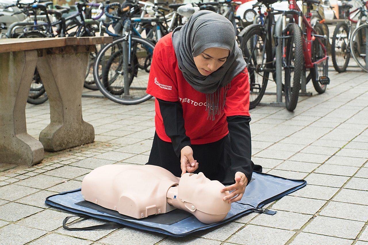 Khadija demonstrates resuscitation on a dummy