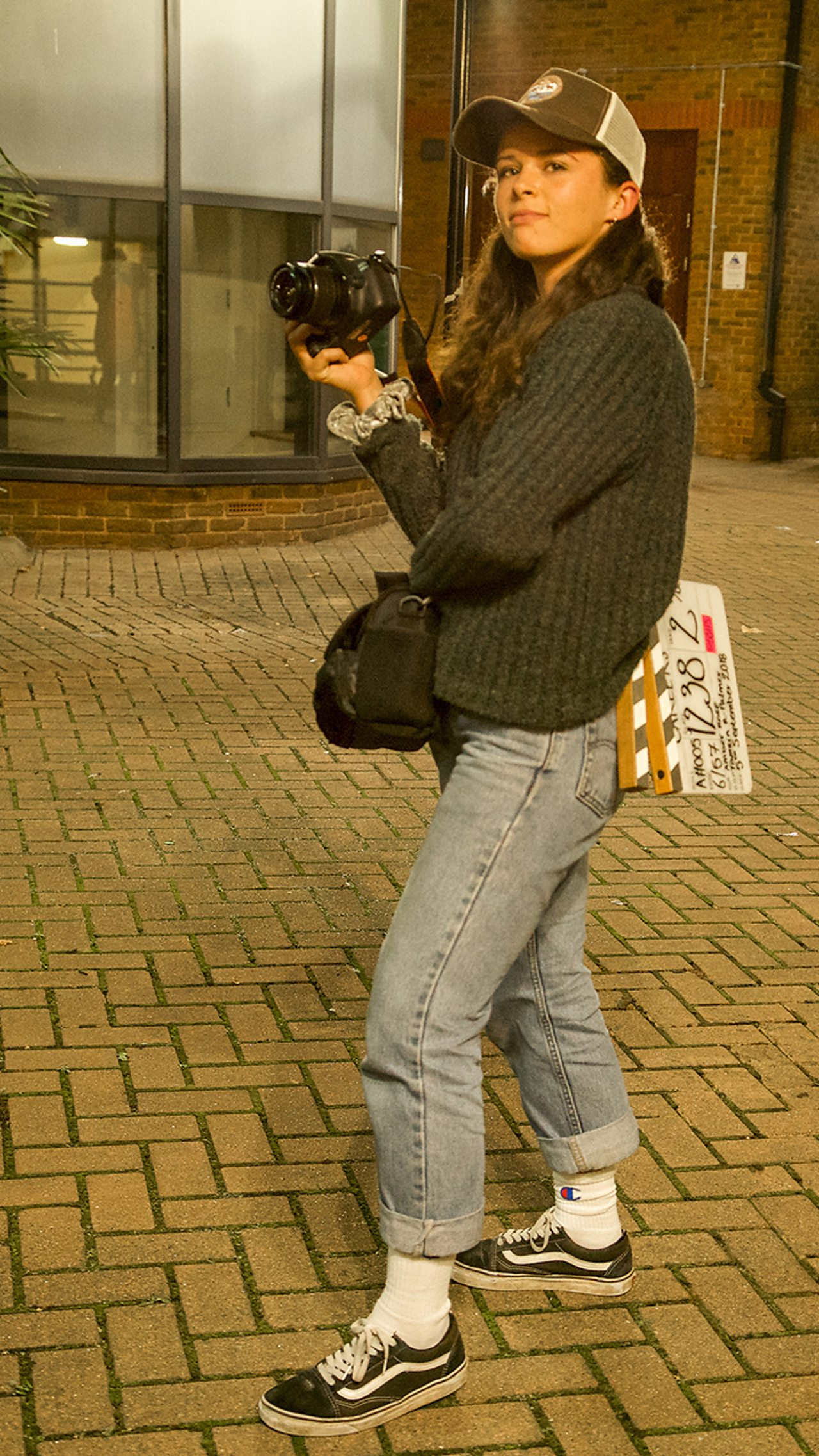 A young woman, Tamsin, standing outside with a camera and a clapper board