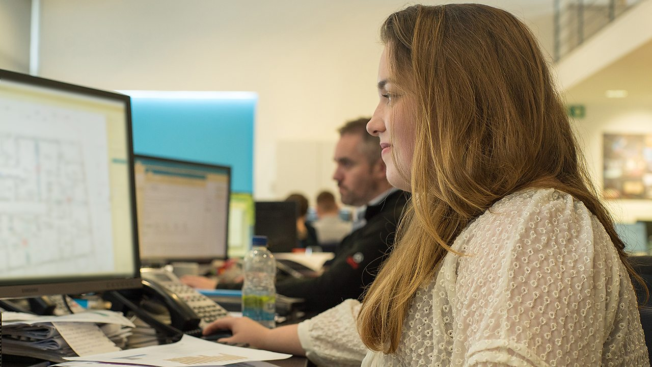 A young woman, Aine, working on her computer in an office environment