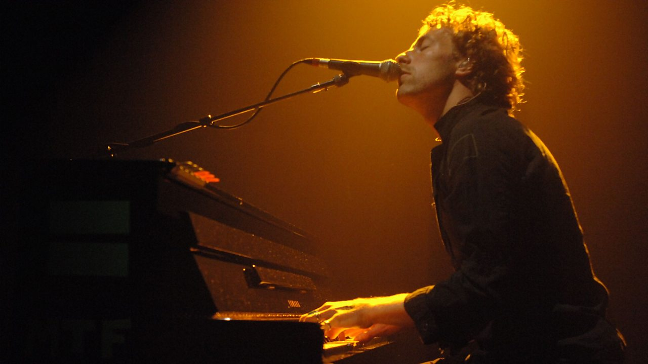Chris Martin from Coldplay singing and playing the piano