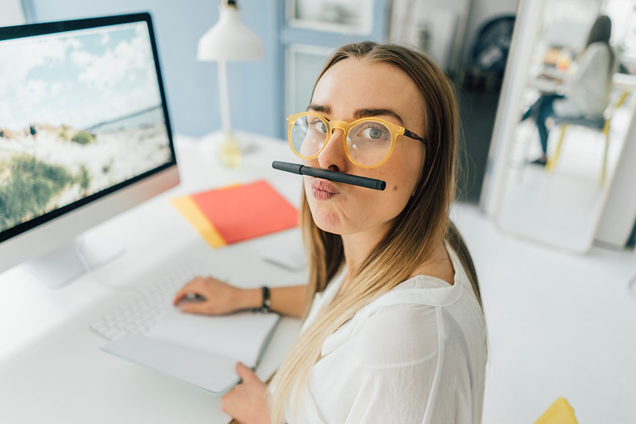 A girl sits at a desk and jokes around making a moustache with a pencil