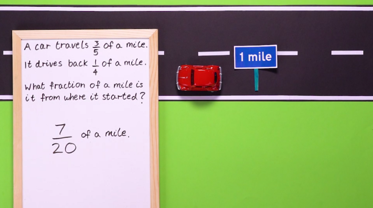 A toy car on a road with a sign saying one mile and a maths problem on a white board