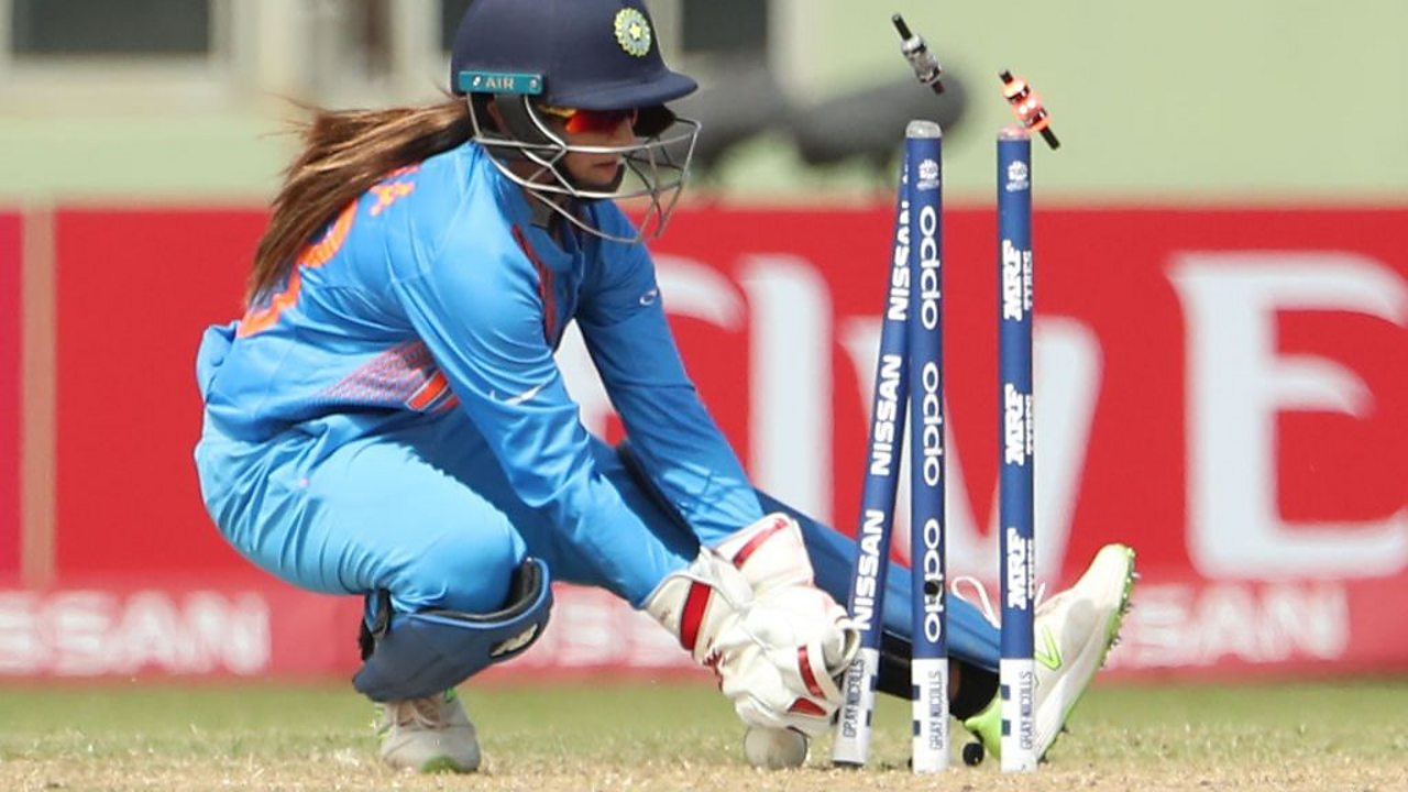 A female cricketer behind a wicket that's just been taken