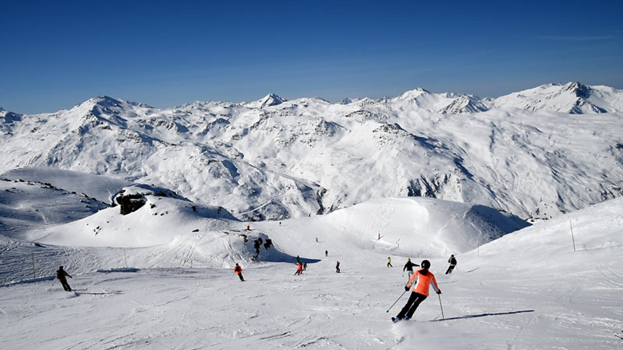 mountains covered in snow with people skiing