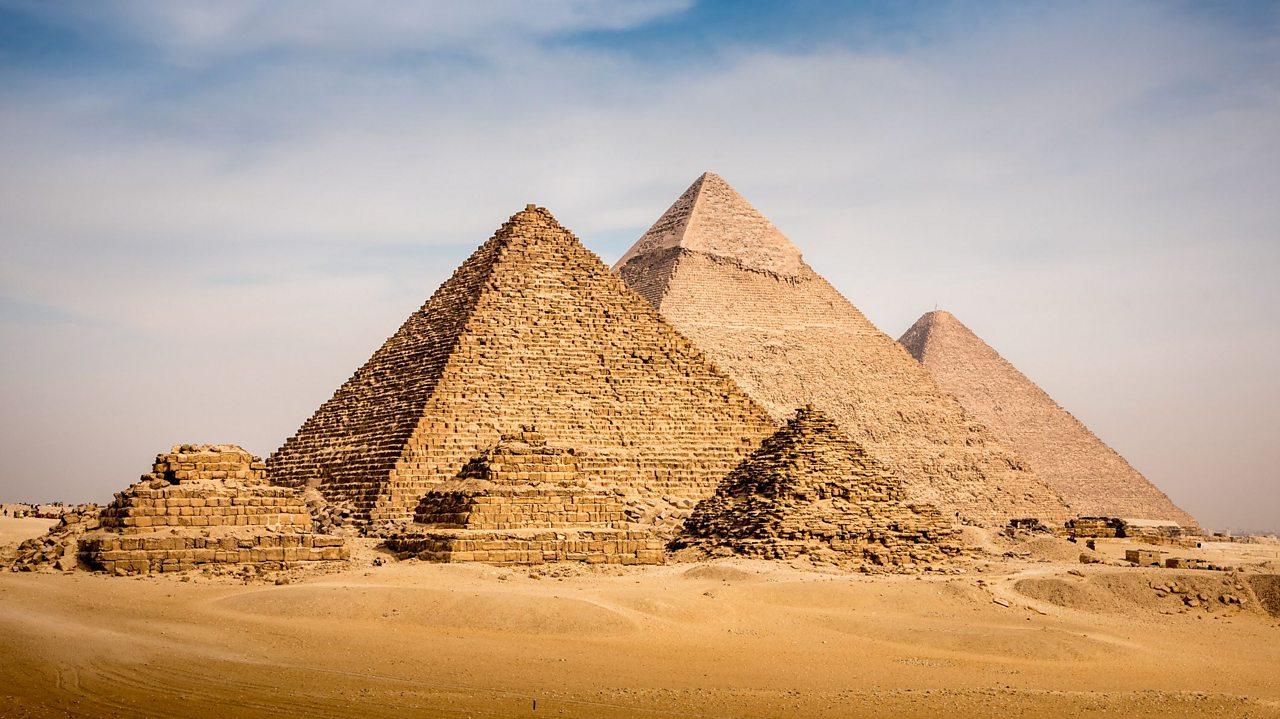 A photo of six pyramids. There are three small pyramids in the foreground and three big pyramids behind them. The tallest pyramid is in the middle at the back.