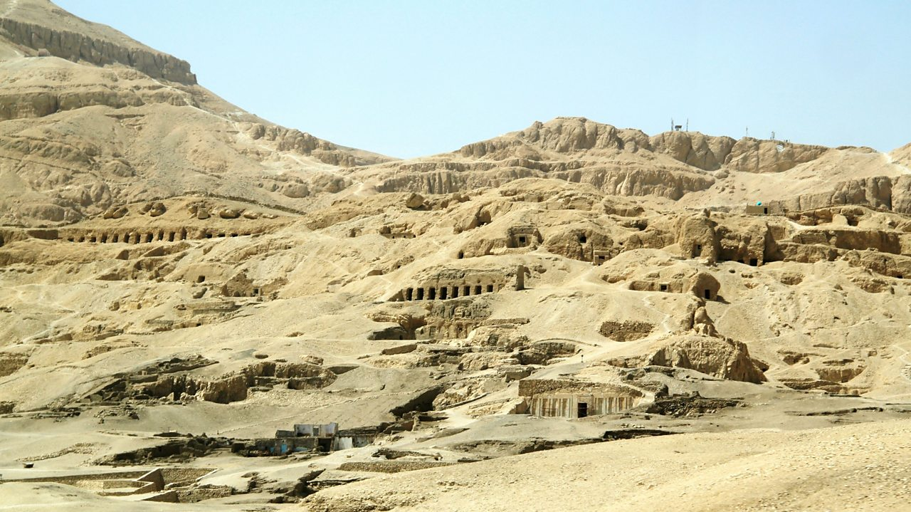 A photo of a wide valley with lots of tombs built into the sandy edges. Lots of small dark entrances are visible in the picture.