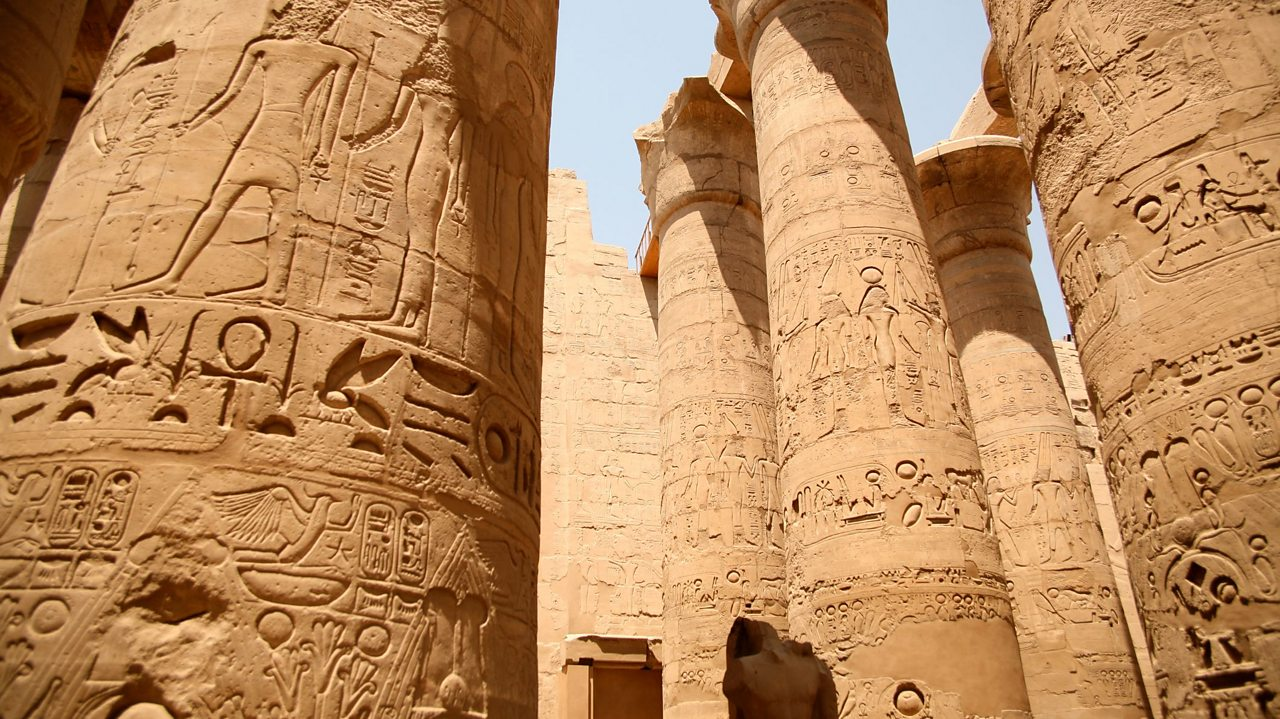 A photo of the huge temple columns at Karnak. The columns have lots of hieroglyphs and pictures of gods carved into them.