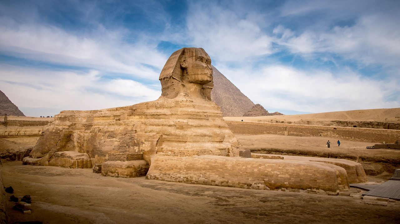 A photo of a limestone sphinx in front of the pyramids of Giza. The sphinx has huge front paws and it's head is carved to look like a man wearing a royal head cloth.