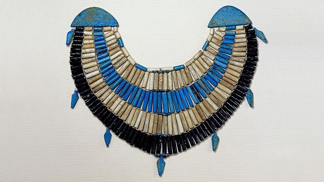 A photo of a blue, white and purple beaded wide collar necklace