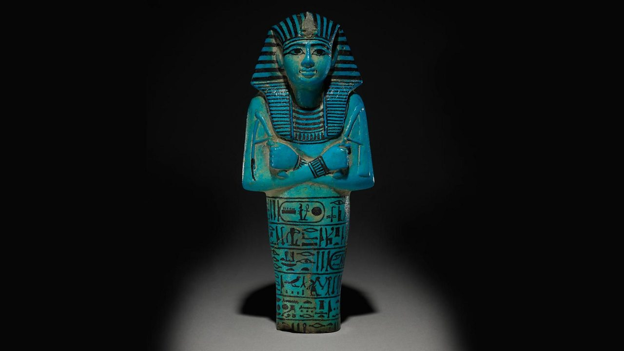 A photo of a blue glazed shabti figure with details painted in black