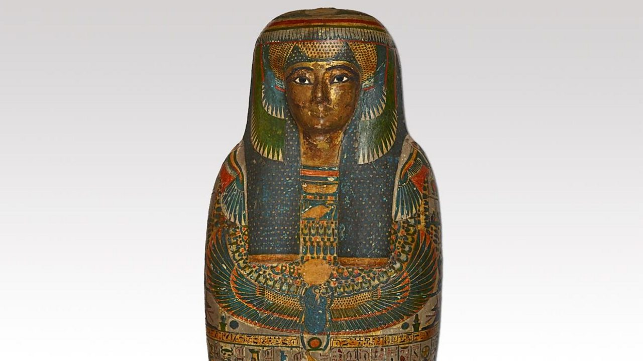 A photograph of a human mummy case with a painted body and a gilded face