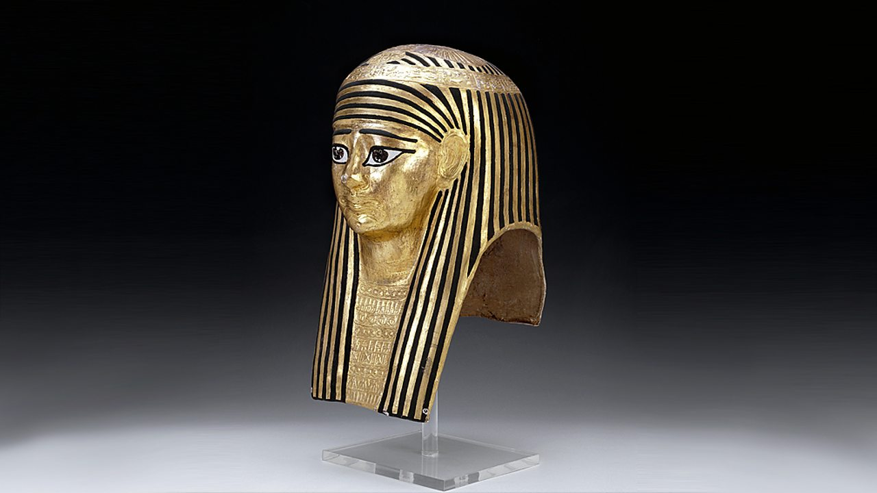 A photograph of a human mummy mask coated in gold leaf