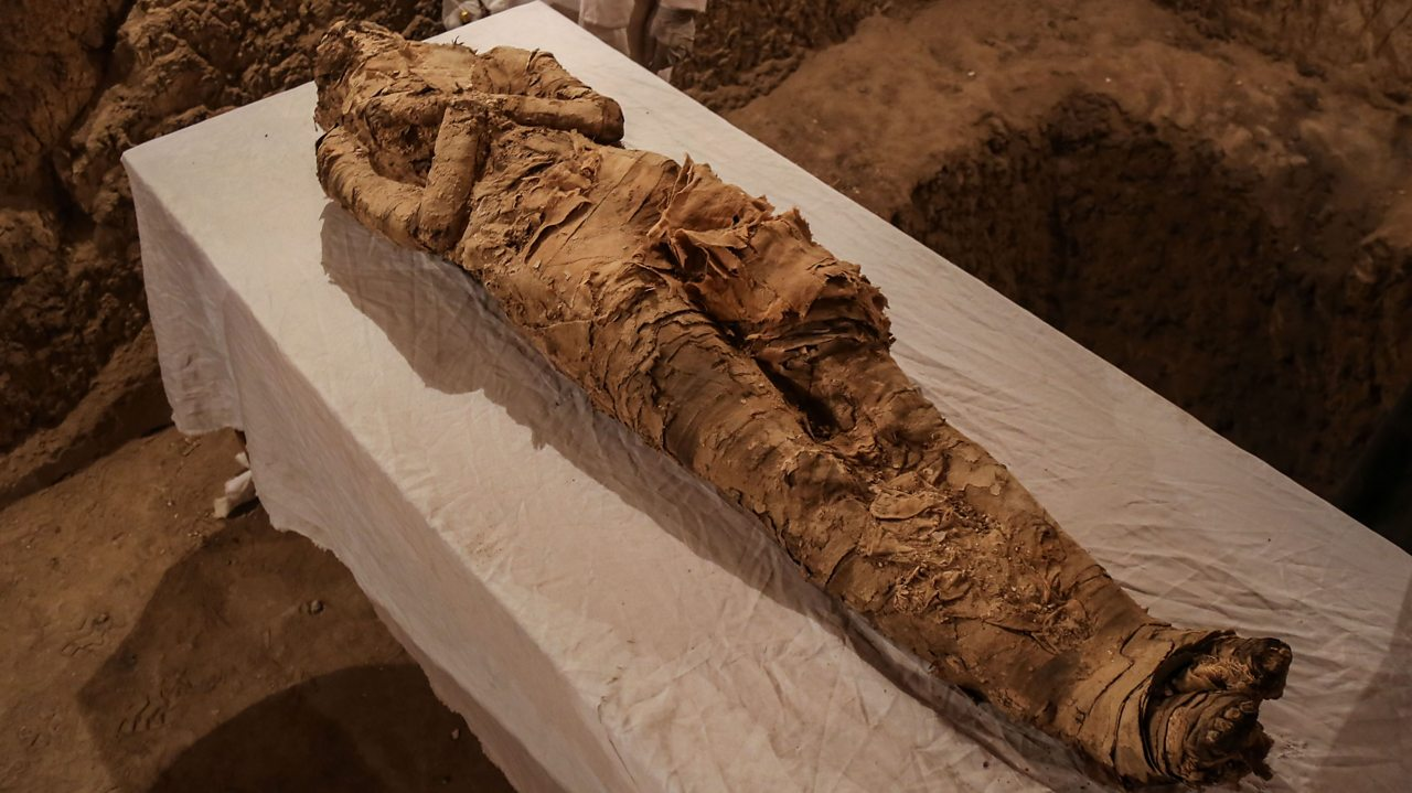 A photo of a scruffy and decayed mummified body found in a tomb in Egypt.