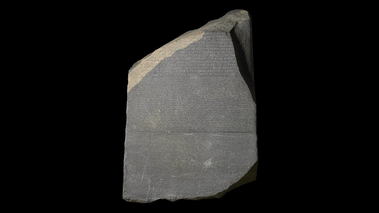 A photo of the famous Rosetta Stone. It is a large, dark grey piece of granite with rough edges. It has inscriptions carved into it.